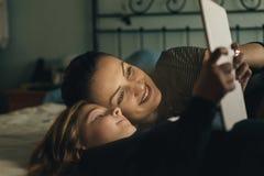 母亲和她的孩子有数字式片剂的 免版税图库摄影