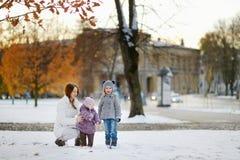 年轻母亲和她的孩子获得乐趣在冬天 免版税库存照片