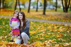 年轻母亲和她的小女儿秋天的 免版税图库摄影