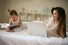母亲和她的小婴孩在家 有她的使用t的婴孩的母亲 免版税库存照片