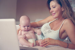 母亲和她的小婴孩在家 图库摄影