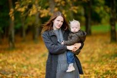 年轻母亲和她的小孩女儿秋天的 库存图片