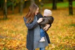 年轻母亲和她的小孩女儿秋天的 免版税库存图片