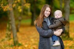 年轻母亲和她的小孩女儿秋天的 图库摄影