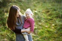 年轻母亲和她的小孩女儿秋天的 免版税库存照片
