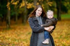 年轻母亲和她的小孩女儿秋天的 免版税图库摄影