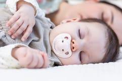 年轻母亲和她的睡觉在床上的女婴 免版税图库摄影