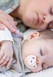 年轻母亲和她的睡觉在床上的女婴 免版税库存图片