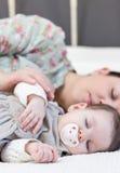 年轻母亲和她的睡觉在床上的女婴 库存图片