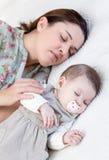 年轻母亲和她的睡觉在床上的女婴 免版税库存照片