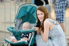 年轻母亲和她的婴孩婴儿推车的 库存图片