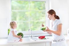 年轻母亲和她逗人喜爱小孩女儿烹调 免版税图库摄影