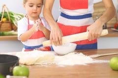 母亲和她逗人喜爱的女儿准备面团在木桌上 面包或薄饼的自创酥皮点心 面包店背景 库存图片