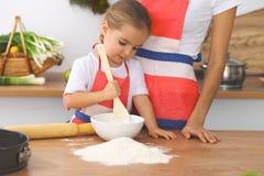 母亲和她逗人喜爱的女儿准备面团在木桌上 面包或薄饼的自创酥皮点心 面包店背景 免版税图库摄影