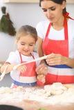 母亲和她逗人喜爱的女儿准备面团在木桌上 面包或薄饼的自创酥皮点心 面包店背景 免版税库存图片