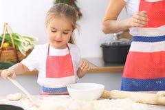 母亲和她逗人喜爱的女儿准备面团在木桌上 面包或薄饼的自创酥皮点心 面包店背景 图库摄影