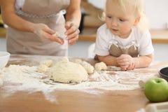 母亲和她逗人喜爱的女儿手准备在木桌上的面团 面包或薄饼的自创酥皮点心 烘烤 免版税库存照片