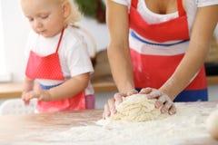 母亲和她逗人喜爱的女儿手准备在木桌上的面团 面包或薄饼的自创酥皮点心 烘烤 库存照片