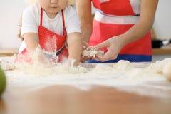 母亲和她逗人喜爱的女儿手准备在木桌上的面团 面包或薄饼的自创酥皮点心 烘烤 免版税库存图片