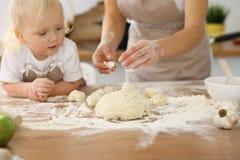 母亲和她逗人喜爱的女儿手准备在木桌上的面团 面包或薄饼的自创酥皮点心 烘烤 库存图片