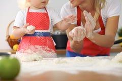 母亲和她逗人喜爱的女儿手准备在木桌上的面团 面包或薄饼的自创酥皮点心 烘烤 免版税图库摄影