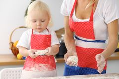 母亲和她逗人喜爱的女儿手准备在木桌上的面团 面包或薄饼的自创酥皮点心 烘烤 图库摄影