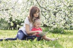 年轻母亲和她逗人喜爱的女儿阅读书 免版税库存图片