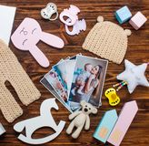 母亲和婴孩图片和与衣裳和玩具在土气木背景 免版税库存照片