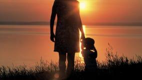 母亲和婴孩横跨领域努力去做河在日落 愉快的系列 影视素材