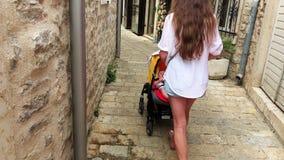 母亲和婴孩沿有摇篮车的狭窄的老镇街道旅行 图库摄影