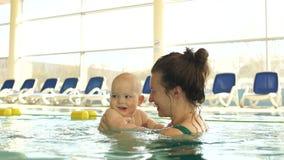 母亲和婴孩获得乐趣在水池 妇女亲吻并且拥抱她的孩子 日花产生母亲妈咪儿子 股票视频