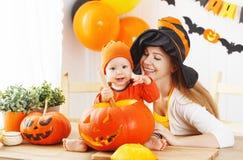 母亲和婴孩裁减南瓜为万圣夜在厨房里 库存照片