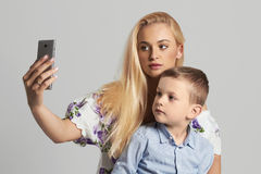 母亲和子项 有小儿子的美丽的白肤金发的妇女 愉快的系列 免版税库存图片