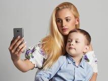 母亲和子项 有小儿子的美丽的白肤金发的妇女 愉快的系列 免版税库存照片