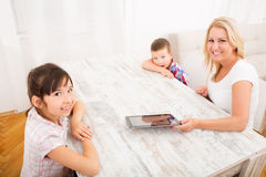 母亲和孩子与片剂个人计算机 库存照片
