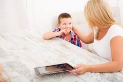 母亲和孩子与片剂个人计算机 免版税库存图片