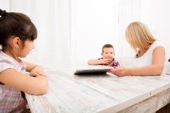 母亲和孩子与片剂个人计算机 库存图片