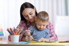 母亲和孩子与色的铅笔的儿子图画 免版税库存照片