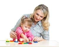 母亲和孩子使用与五颜六色的难题玩具 库存照片