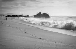 母亲和孩子剪影获得在沙滩的乐趣与波浪热的晴天在大西洋海岸的10月在黑白, 库存图片