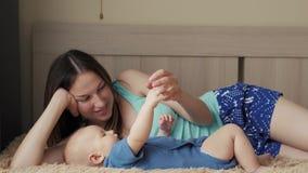 母亲和孩子在一张白色床上 妈妈和男婴使用在晴朗的卧室的尿布的 放松在的父母和小孩 股票录像