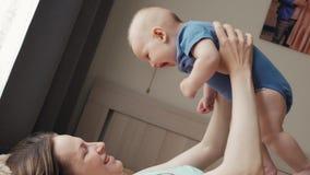 母亲和孩子在一张白色床上 妈妈和男婴使用在晴朗的卧室的尿布的 放松在的父母和小孩 股票视频