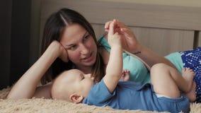 母亲和孩子在一张白色床上 妈妈和男婴使用在晴朗的卧室的尿布的 放松在的父母和小孩 影视素材