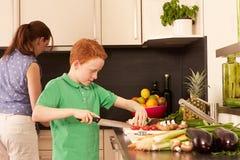 母亲和孩子在厨房里 图库摄影