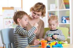 母亲和孩子在家获得一个乐趣 库存图片