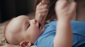 母亲和孩子在床上 妈妈和男婴使用在晴朗的卧室的尿布的 的父母和在家放松的小孩 股票视频