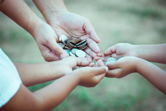 母亲和孩子在手上的拿着硬币 免版税库存图片