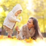 母亲和孩子在秋天公园 库存图片