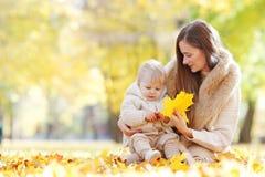 母亲和孩子在秋天公园 免版税库存图片