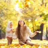 母亲和孩子在秋天公园 免版税库存照片